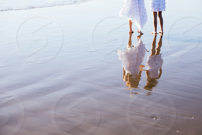 two women in white dresses standing on the beach photo