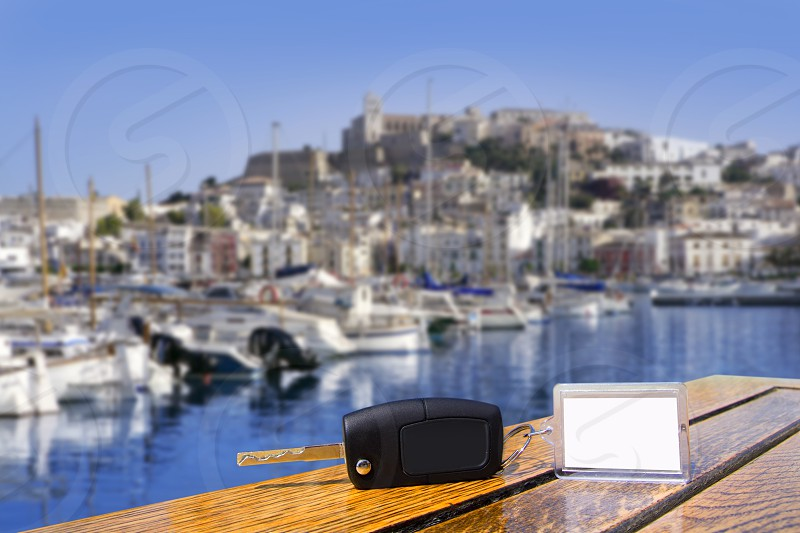 Car rental keys on wood table with blank paper in Ibiza town Mediterranean island photo