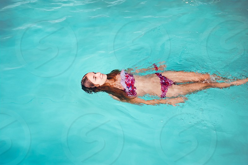 Young woman swimming and relaxing in swimming pool. Candid people real moments authentic situations photo