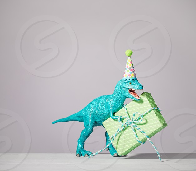 T-rex dinosaur toy with birthday hat holding gift on a light grey background. photo