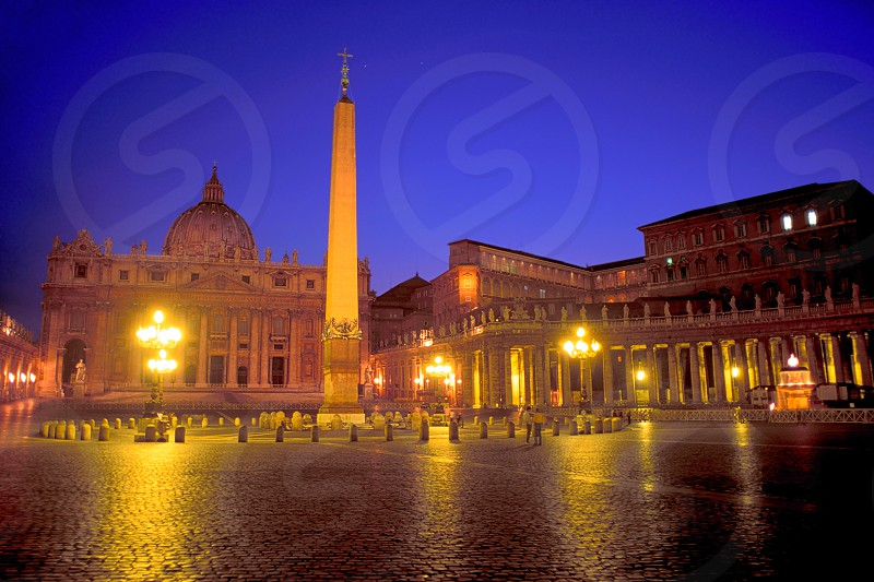 An evening in St. Peter's square in Rome Italy. The lights in the Pope's quarters are on. photo