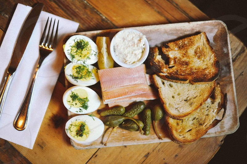 four hard boiled egg halves with sliced meat toast pickles and spread on a wood table next to a silver knife and fork on a white napkin photo