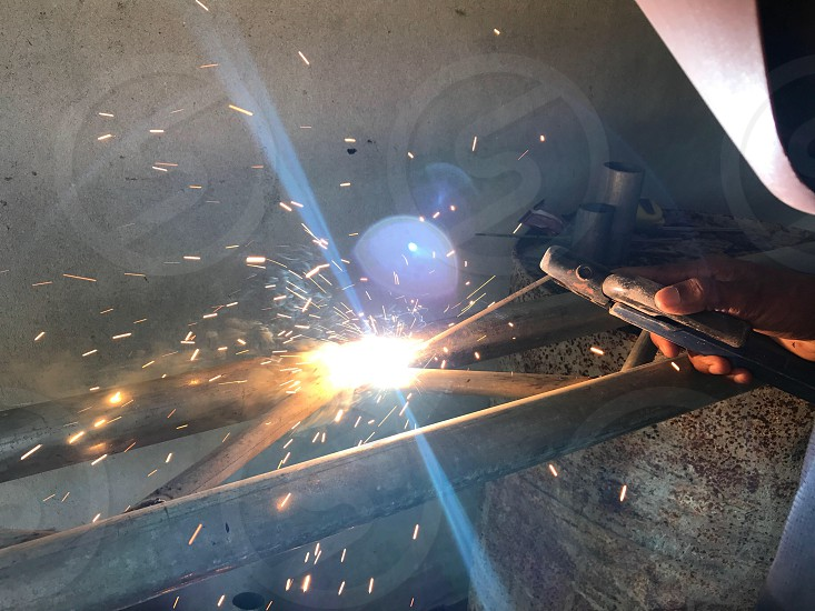 Welding welder metal work worker flames flash fumes cutting machines pipes rod photo