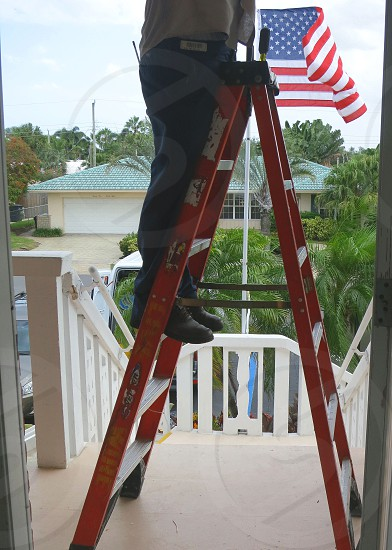 Man working on ladder to accompaniment of furling flag photo