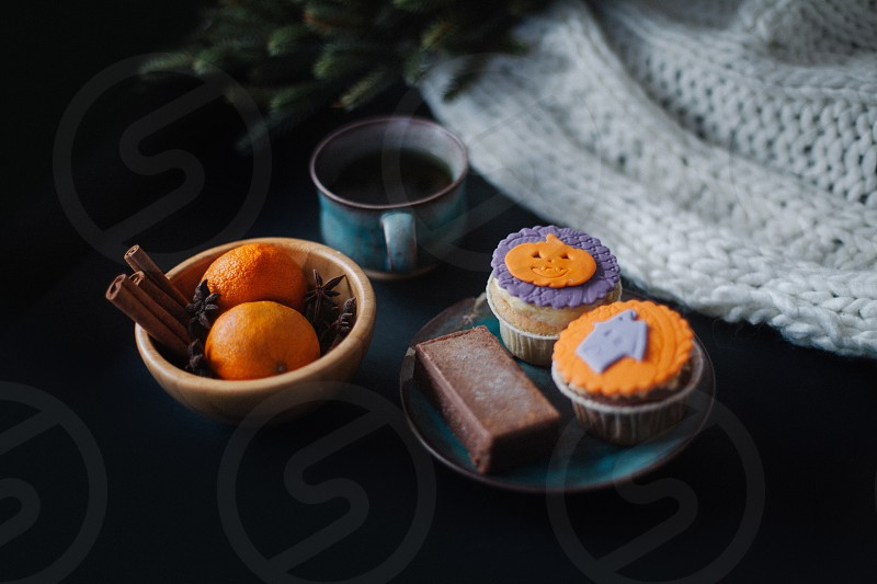 2 orange fruits in brown round bowl near chocolate bar with 2 cupcakes on blue round saucer photo