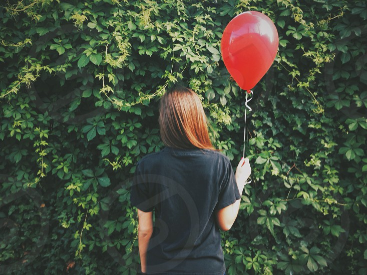 woman wearing a black t shirt holding a red balloon photo