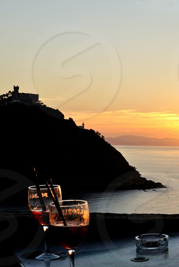 two people in red wine watching the sunset photo