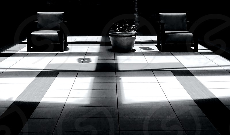 Stark light on two chairs in the lobby of a mall. photo