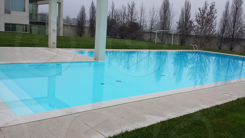 swimming pool near green grass under cloudy sky during daytime photo