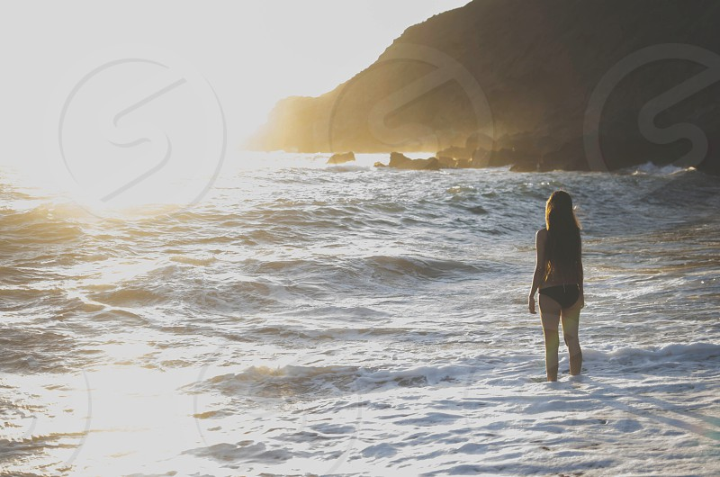 girl standing at the seashore looking at the horizon while waves are breaking at golden hour  photo