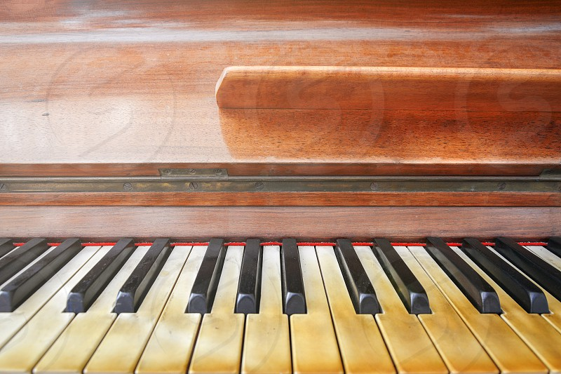 Keyboard of a well worn piano. Frontal view photo