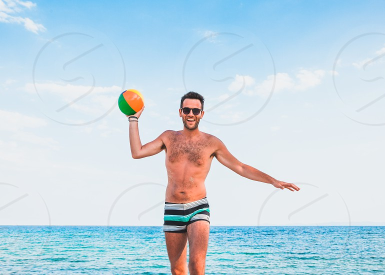 Young handsome man at the beach trowing the ball into the camera photo