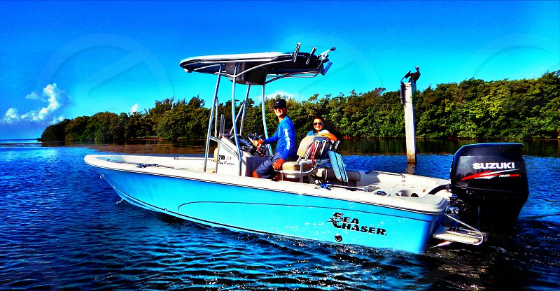 two person riding on white and blue outboard boat photo