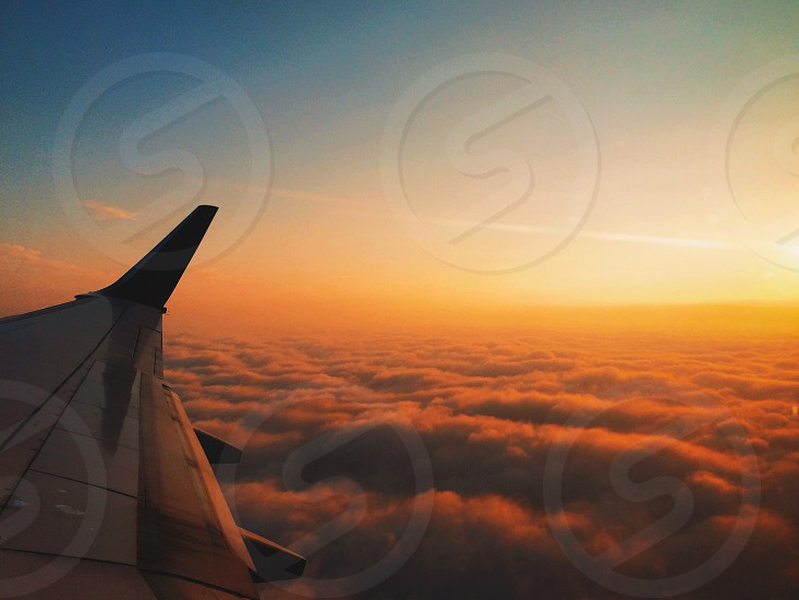 photo of a airplane wing with thick cloud under photo