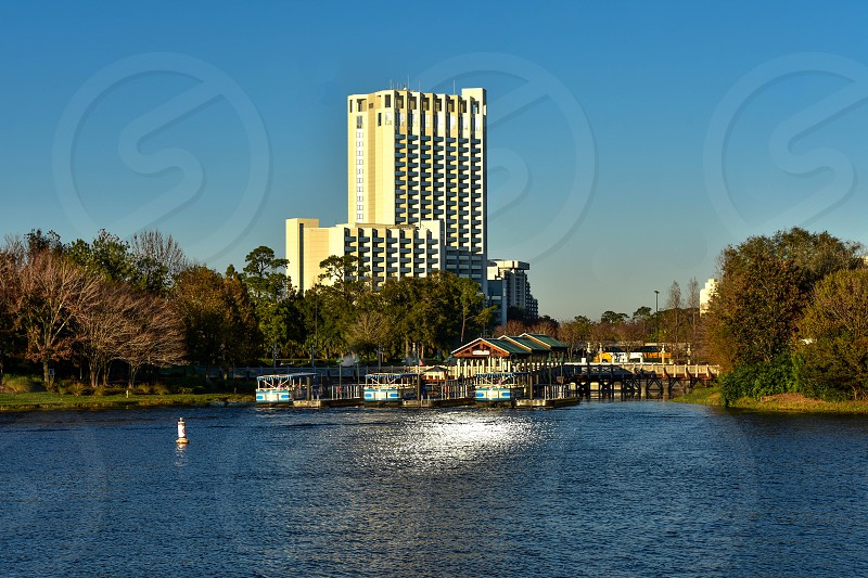 Orlando Florida. January 2019.  Wharf of Water taxis and forest with autumn colors on Lake Buena Vista Hotel background. photo