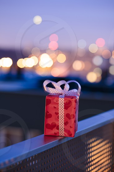 Christmas gift left on railing of balcony with blurred lights in the background photo