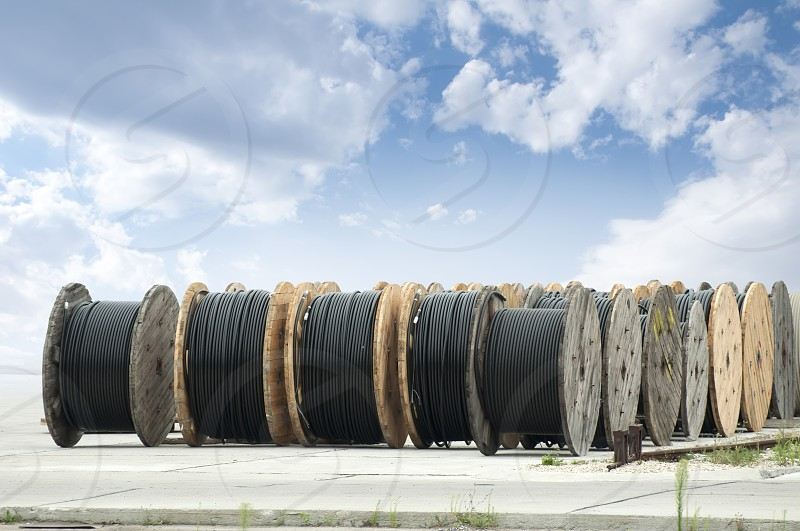 Large rolls of black cables on blue sky background photo