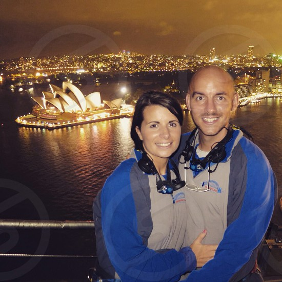 A couple at the top of the Sydney Harbour Bridge at night with the Sydney Opera House in the background. photo