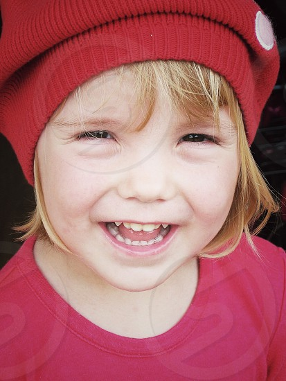 girl in red beanie smiling photo