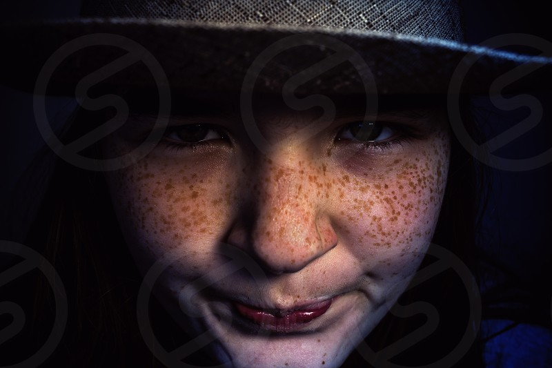 Studio portrait of a young girl wearing a hat and smiling. photo