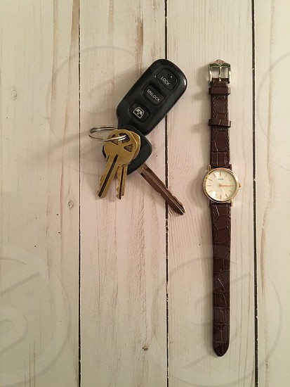 brown leather strap gold round analog watch beside black car fob photo