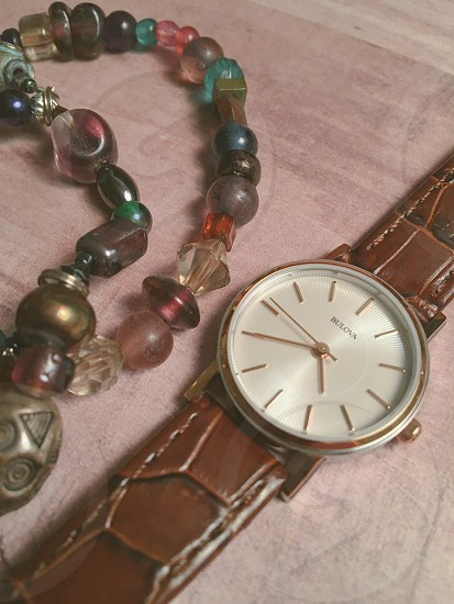 brown leather strap silver analog watch reading at 4:35 photo