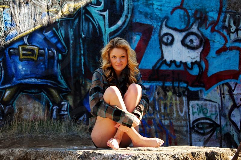 Blonde Woman Sitting On Rock With Graffiti Background photo