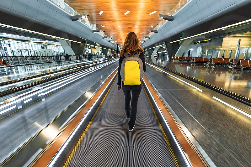 One woman traveller with backpack go on moving walkway travolator in new Hamad International Airport. Back view photo