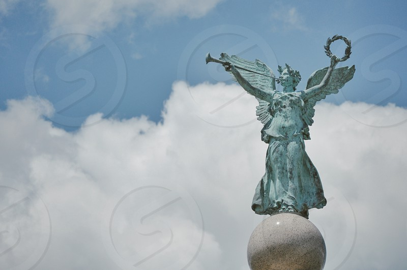 angel blowing horn themed statue under a white cloud formation during daytime photo
