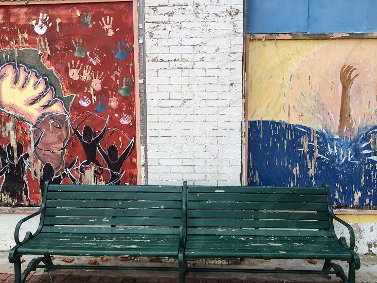 Green park bench against graffiti on historic Farrish Street in Jackson MS.  photo