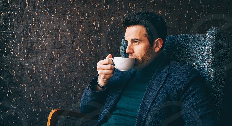 Young man drinking a coffee at the cafe photo