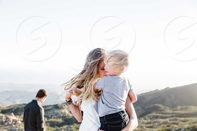 blonde boy toddler being held by mom in white on a hillside with dad in the distance photo