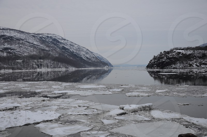body of water partly covered with ice with rocky mountain background under gray sky photo