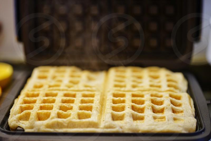 Baking fresh waffles for breakfast photo