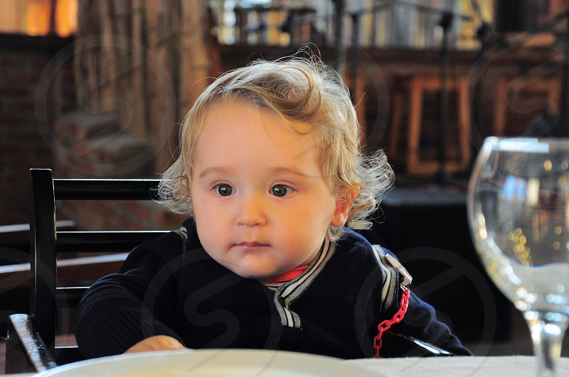 baby in black sweater near white plate at table photo