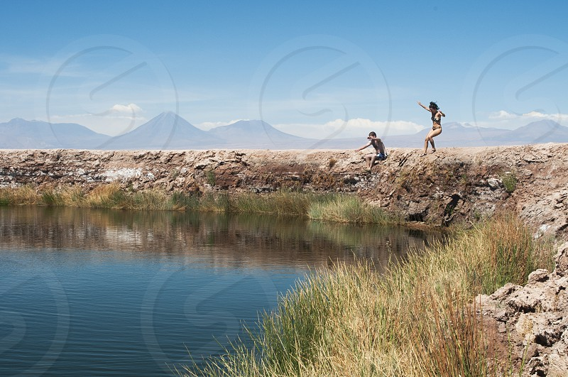 vibrant active outdoors summertime shot of girl and boy jumping to a lake in the middle of the desert with mountains and incredible landscape in the backgroung with blue sky and mountains photo