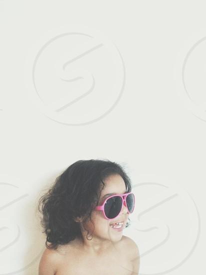 child wearing pink framed sunglasses photo