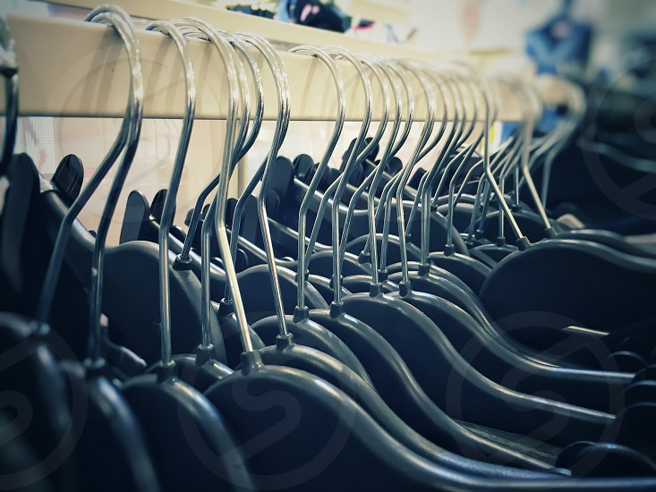 close-up view of a group of clothes hangers hanging in a row inside a shop photo