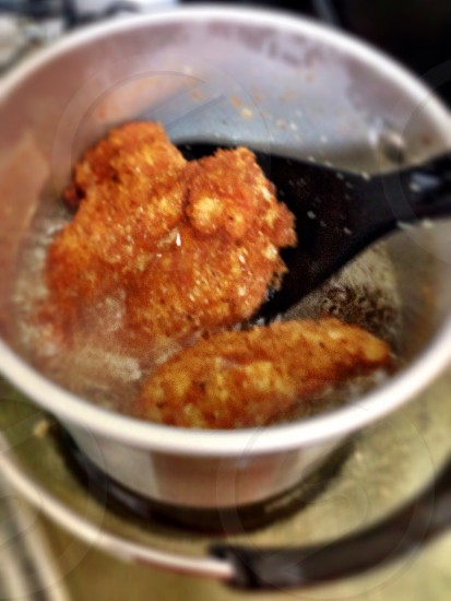 black spoon holding breaded fried meat in round cup photo