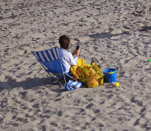 Woman in beach chair checking phone photo