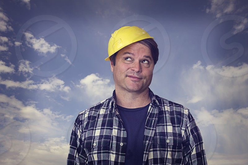 Tradesman wearing a too-small construction safety hat photo
