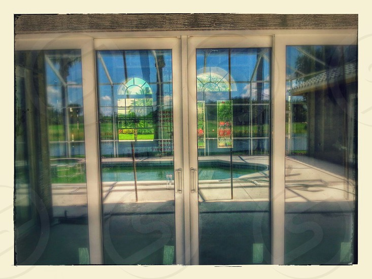 Reflection of a pool and backyard in a set of sliding glass doors photo