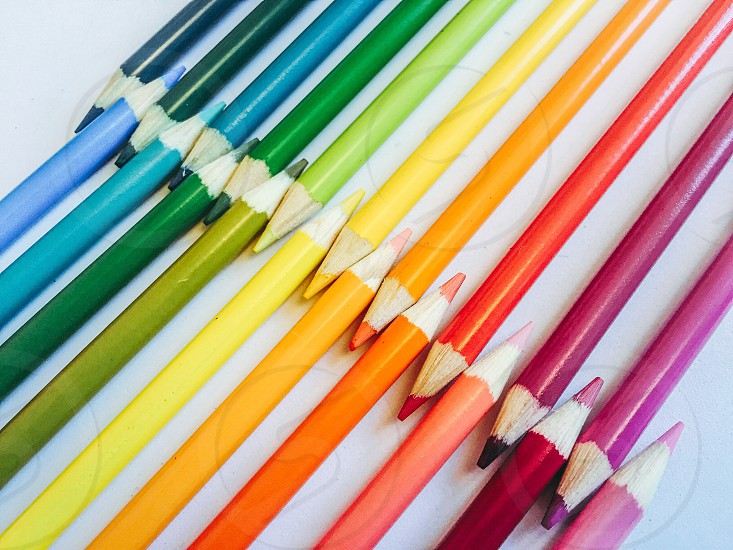 A Rainbow spectrum of brightly coloured pencils organised  in a geometric pattern photo