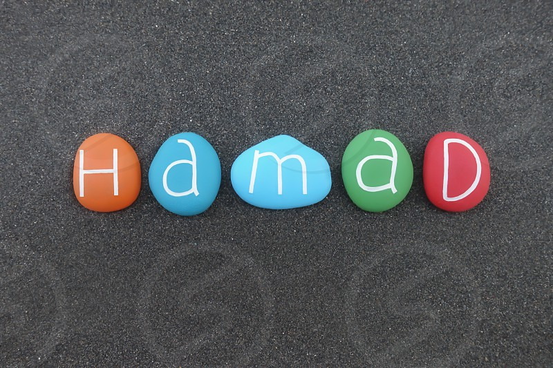 Hamad arabic masculine name composed with multi colored stones over black volcanic sand                            photo