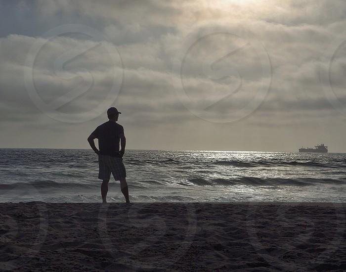Beach man thinking reflecting pondering moment waves California  photo