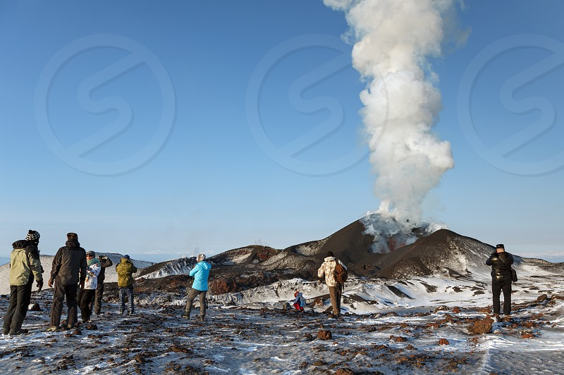 TOLBACHIK VOLCANO KAMCHATKA PENINSULA RUSSIAN FAR EAST - FEBRUARY 2 2013: Tourists watching the eruption of active Tolbachik Volcano erupting from crater lava ash steam and gas. Russia Far East Kamchatka Peninsula. photo
