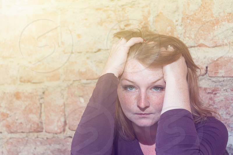 Stressed redhead young woman is holding her head by both hands and is looking at the camera. Old brick wall is in the background. photo