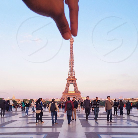 people walking in front of eiffel tower with hand holding the eiffel tower on its tip photo