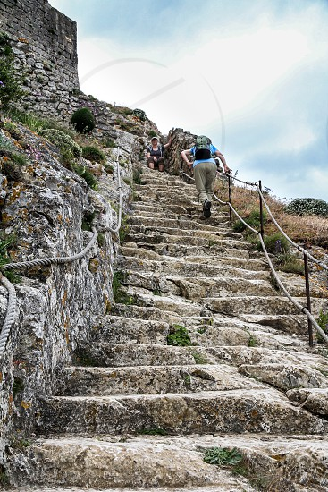 two women climbing stairs at the ruined Cathar castle of Château de Quéribus in France photo