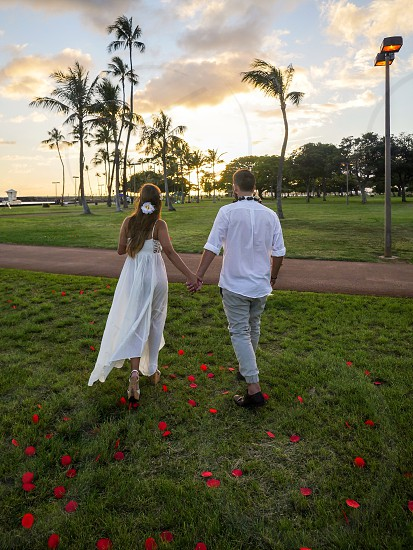 Couple holding hands at the park walking toward the sunset from behind Love romance honeymoon photo